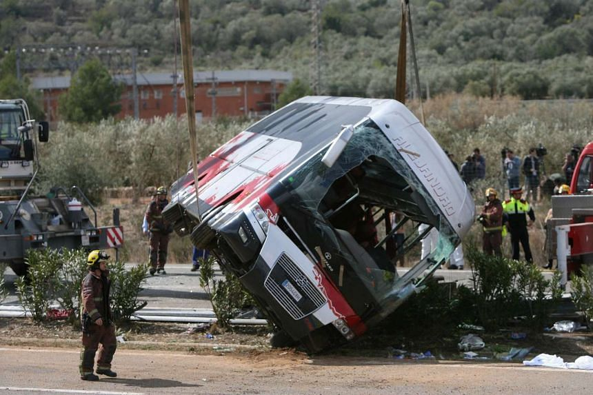 Firemen work at the site of a coach crash that has left at least 14 students dead at the AP-7 motorway in Freginals, in the province of Tarragona, northeastern Spain, on March 20, 2016.
