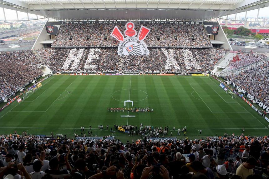 Fans of Corinthians cheer for their team before their Brazil Serie A soccer match against Sao Paulo, at Arena Corinthians stadium, which was built by Odebrecht SA, in Sao Paulo, in this Nov 22, 2015 file photo.