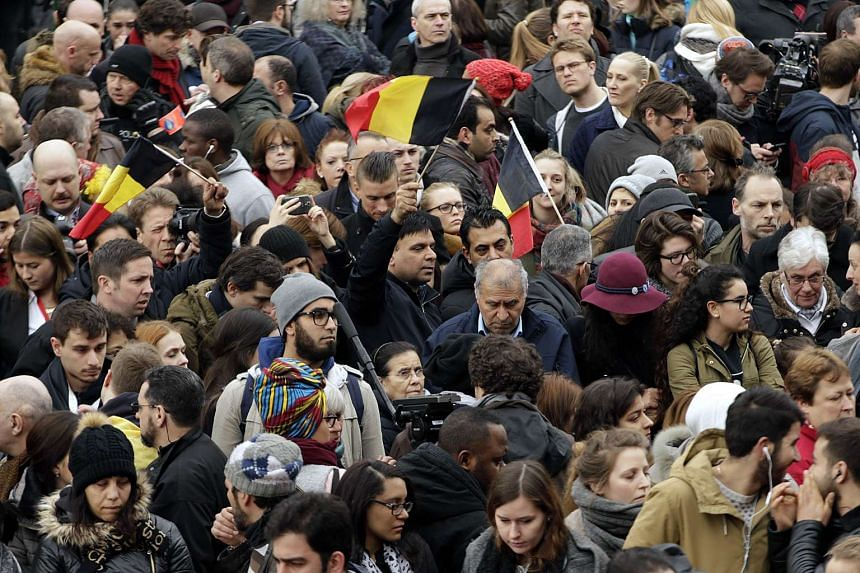 People hold a minute of silence at Place de la Bourse (Beursplein) in Brussels on March 23, 2016,a day after blasts hit the Belgian capital.