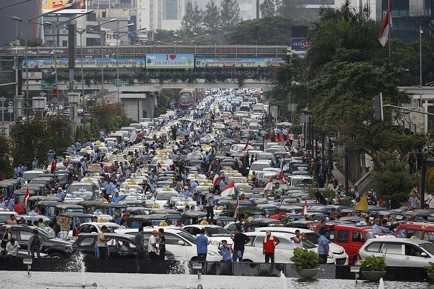 """Taxi drivers protesting against ride-hailing app services on a main street in Jakarta yesterday. Many called for a ban on services like Uber and Grab, calling them """"illegal"""" and said they halved the incomes of regular cabbies."""