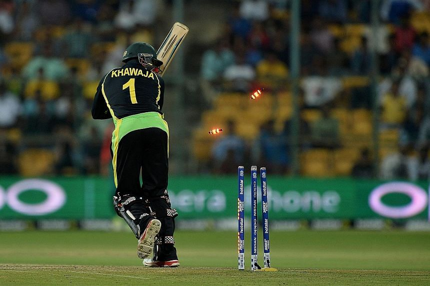 Australia's Usman Khawaja is bowled by Al-Amin Hossain of Bangladesh in the World T20 match in Bangalore on Monday. Australia and hosts India were both beaten earlier by New Zealand, making their quest for a semi-finals spot a lot harder.