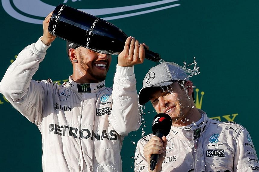 World champion Lewis Hamilton (left) sprays champagne on his Mercedes team-mate Nico Rosberg after the Australian Grand Prix on Sunday. The Briton faces a double challenge, from Rosberg and the two Ferrari drivers, Sebastian Vettel and Kimi Raikkonen