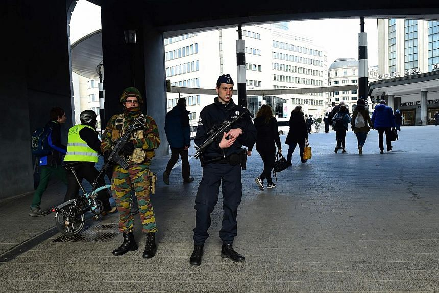 A Belgian police officer and a soldier take position outside Brussels Central Station on March 22, 2016.