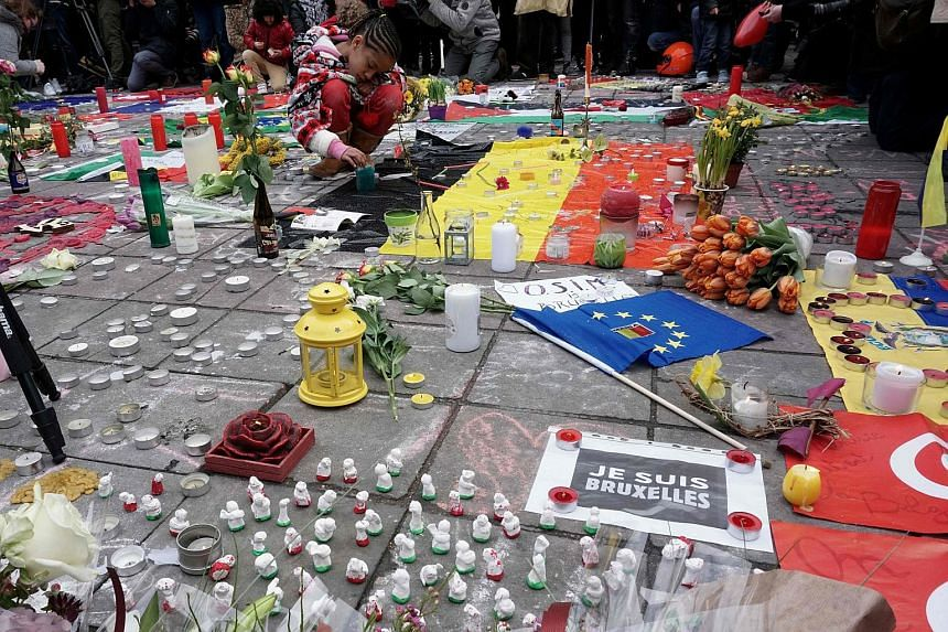 People leave flowers and candles in memory of the victims of the Brussels airport and metro bombings on March 23, 2016.