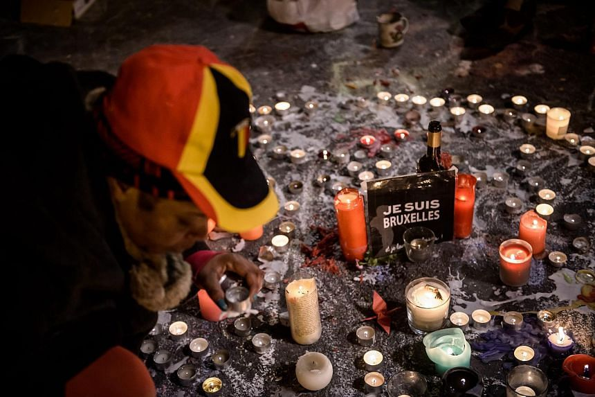 People gather and light candles at the Place de la Bourse during a vigil to pay tribute to the victims of the attacks in Brussels.