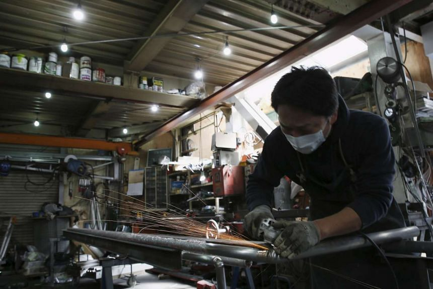 An engineer making arm rails for residential buildings inside a metal processing factory in downtown Tokyo on March 22.