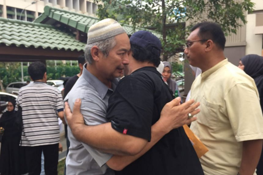 Mr Nasrulhudin's father embracing well-wishers before they headed to the mosque for prayers on March 23, 2016.