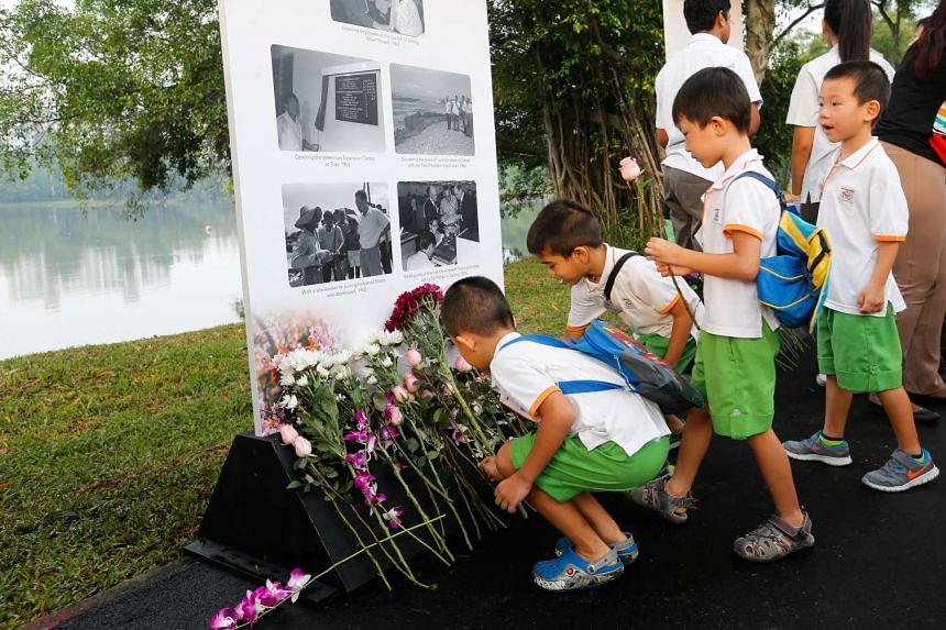 Children laying flowers in front of a memorial site for Mr Lee at Jurong Lake Park.