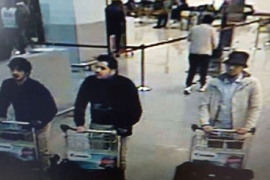 A picture released on March 22, 2016 by the Belgian federal police on demand of the Federal prosecutor shows a screengrab of the airport CCTV camera showing suspects of this morning's attacks at Brussels Airport, in Zaventem.