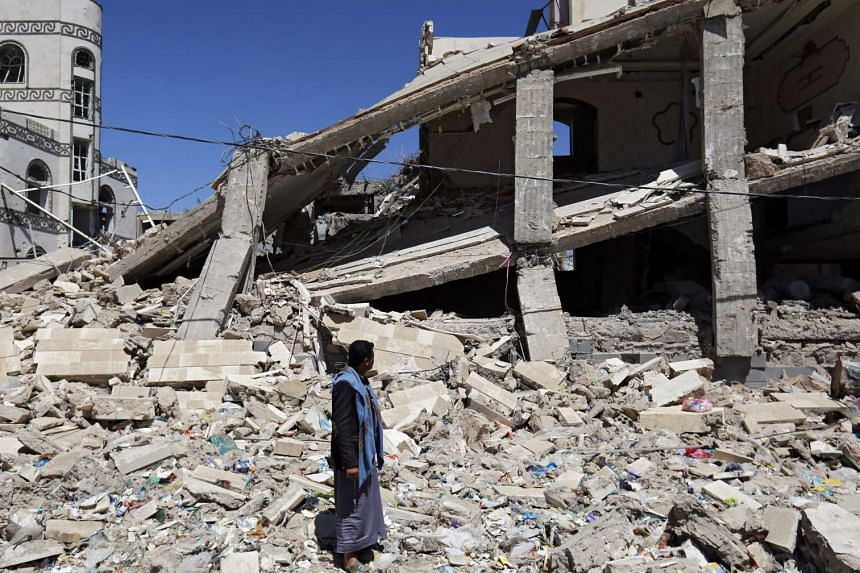 A Yemeni inspecting a building which was targeted by Saudi-led air strikes in Sana'a on March 21.