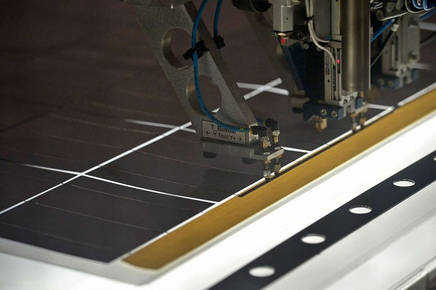 Robots operating on solar panels at the module production line at REC Solar ASA manufacturing facility in Tuas.
