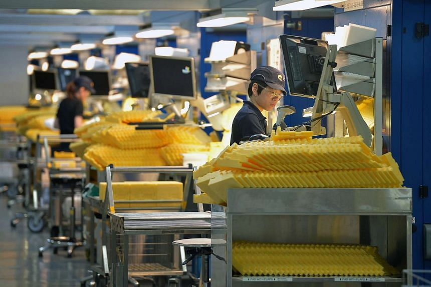 Employees working at the wafer production line at REC Solar ASA manufacturing facility in Tuas.