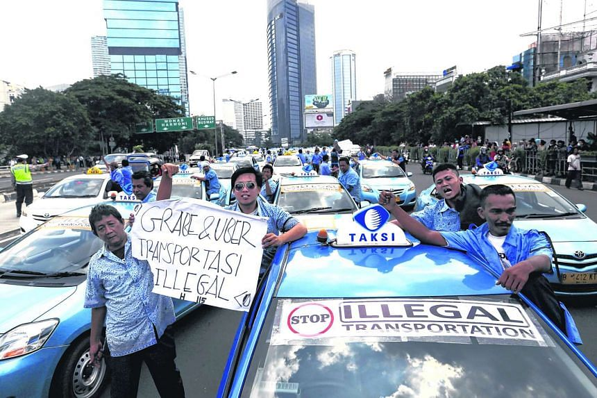 """Taxi drivers stand beside a taxi, with a sign that reads """"Illegal transportation Grab, Uber"""", during a protest rally against transportation apps in Jakarta on March 22, 2016."""