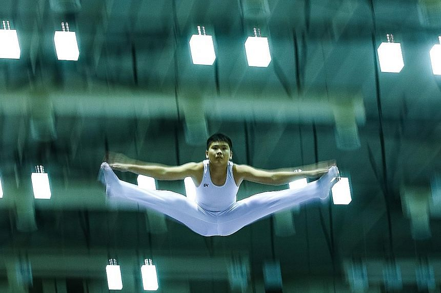 Choong Yih Herng (right) of Hwa Chong Institution (HCI) performs his routine during the B Division competition at the Schools National Gymnastics (Trampoline) Championships at Bishan Sports Hall yesterday. HCI swept the boys' titles in the A, B and C
