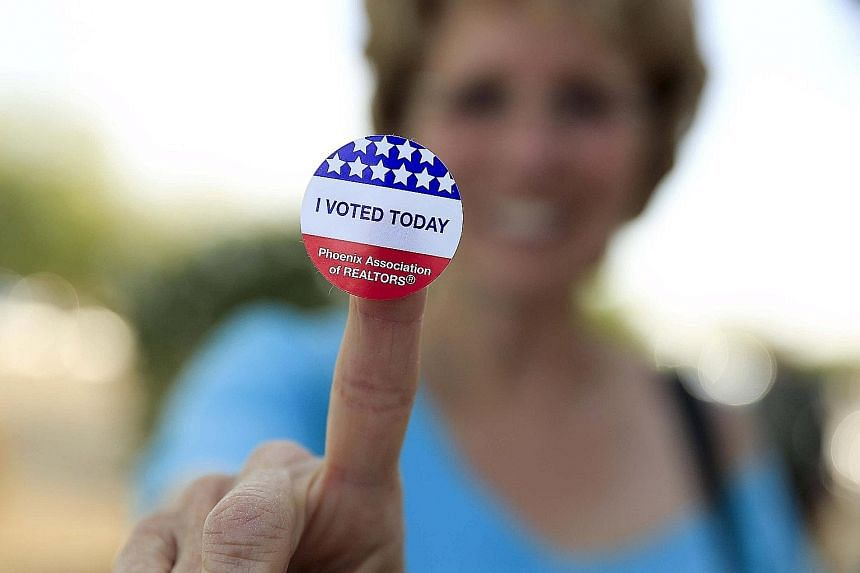 A woman showing off her voting sticker outside a polling site in Glendale, Arizona, on Tuesday. Democratic favourite Hillary Clinton now has 1,681 of the 2,383 delegates required to win the nomination, while Republican front runner Donald Trump's del