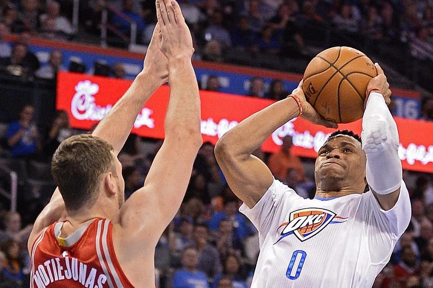 Donatas Motiejunas (far left) of the Houston Rockets trying to block a shot by Oklahoma's Russell Westbrook during the hard-fought 111-107 win by the Thunder.
