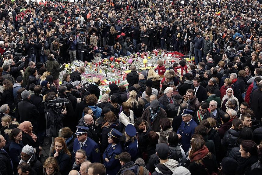 People observing a minute of silence around a makeshift memorial at Place de la Bourse in Brussels yesterday, a day after blasts hit the Belgian capital, killing 31 people and injuring some 270 others. World leaders united in condemning the carnage a