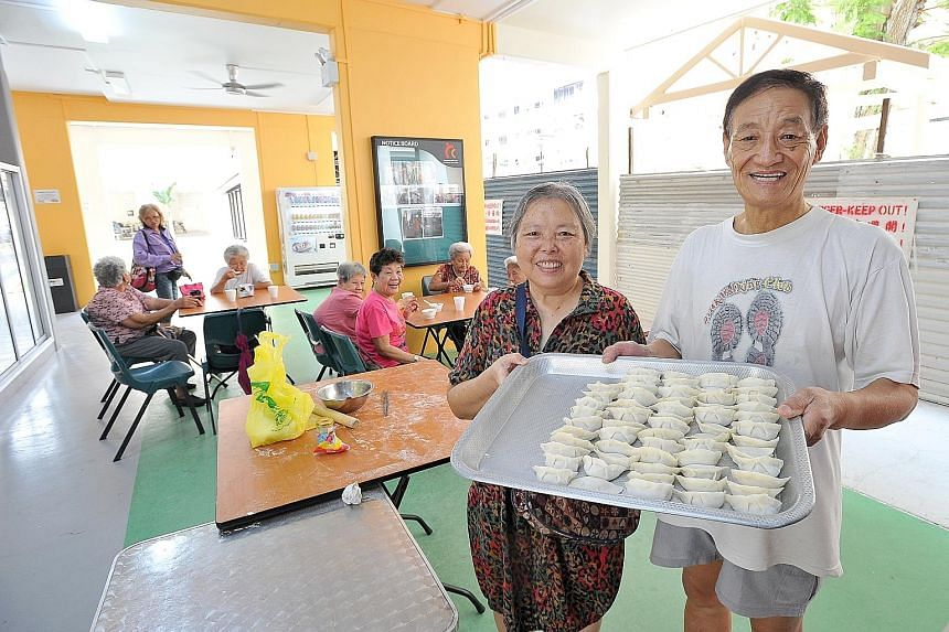 Madam Chen Yuemei (left), 68, and her husband, Mr Wang Ye, 69, both retirees, teach elderly residents how to make dumplings at Palmwalk Cafe Corner, which is located at the void deck of Block 839, Tampines Street 83. The newly opened community cafe i