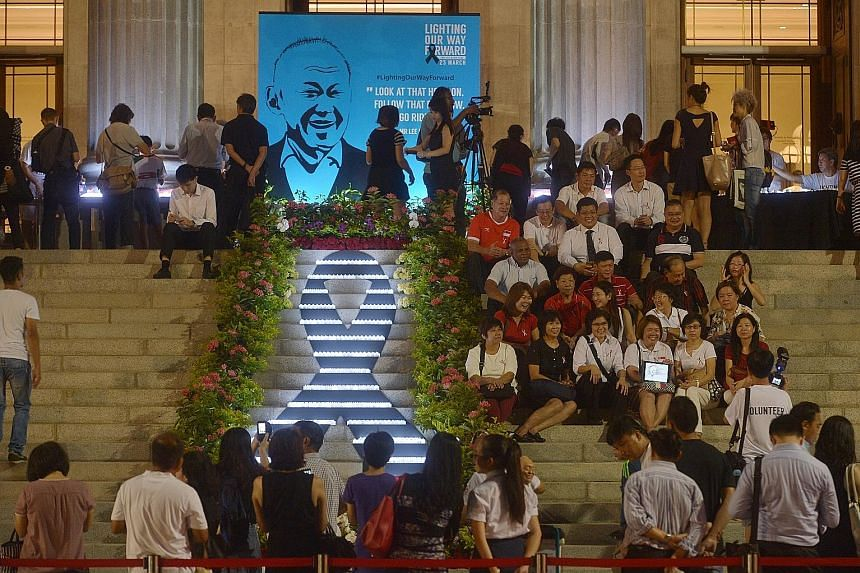 Volunteers and partners of the People's Association laying flowers at a remembrance site for Mr Lee at Istana Park yesterday. At the National Gallery, on the steps of the former City Hall, a group of volunteers formed an illuminated ribbon with elect