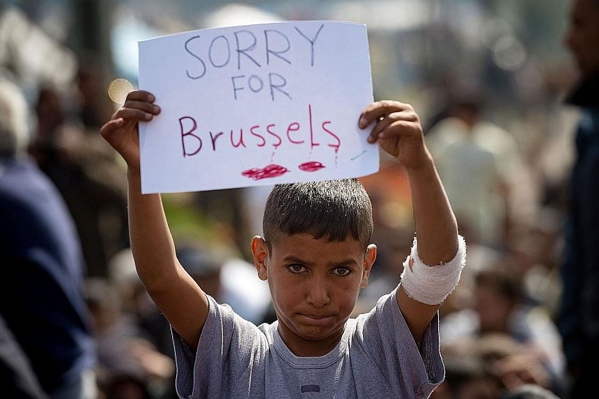 A boy expressing sympathy for the victims of the terror attacks in Brussels during a protest at a makeshift camp at the Greek-Macedonian border near the village of Idomeni on Tuesday. The attacks prompted new questions about European solidarity and s