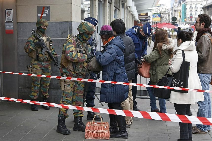 Troops searching people entering a subway station in Brussels yesterday. The Belgian capital was in a lockdown for most of Tuesday.