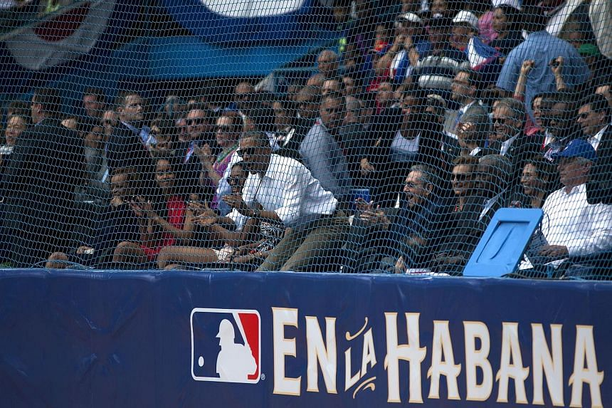 US President Barack Obama (in white shirt) and, at his left, Cuban President Raul Castro at an exhibition game between the Cuban and US baseball teams in Havana on Tuesday. The US leader travelled to Argentina after his historic Cuban visit.