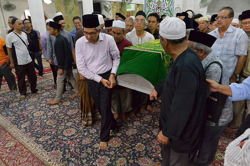 Dr Yaacob carrying the coffin of writer Dr Ariff, alongside family members, yesterday. The minister said Dr Ariff was a pioneer who made tremendous contributions to the community.
