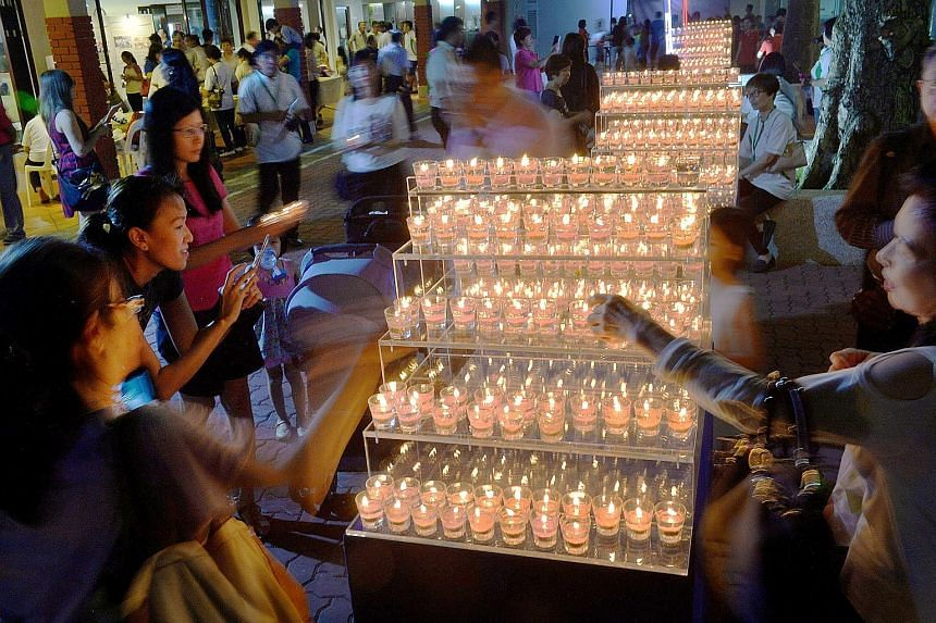 Gel candles, which were handmade by residents and grassroots volunteers, being lit at Tanjong Pagar Community Club last night, to mark the first anniversary of Mr Lee's death. Some did what Mr Lee would have done: they went on a brisk walk across tow