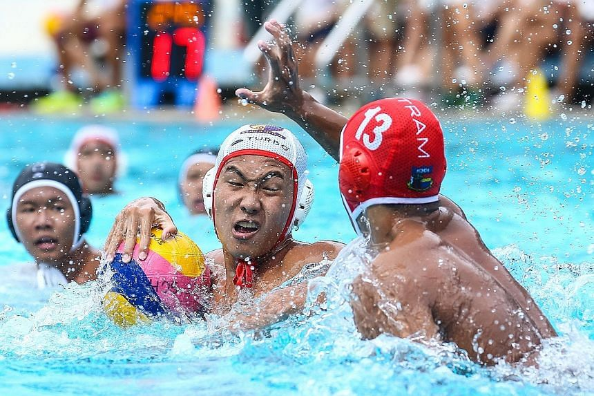Chan Tze Kai of ACS(I) protecting the ball against Tan Zheng Yu of Outram during the B Division water polo final. Playing against their senior A Division boys in training helped build up ACS(I)'s confidence.