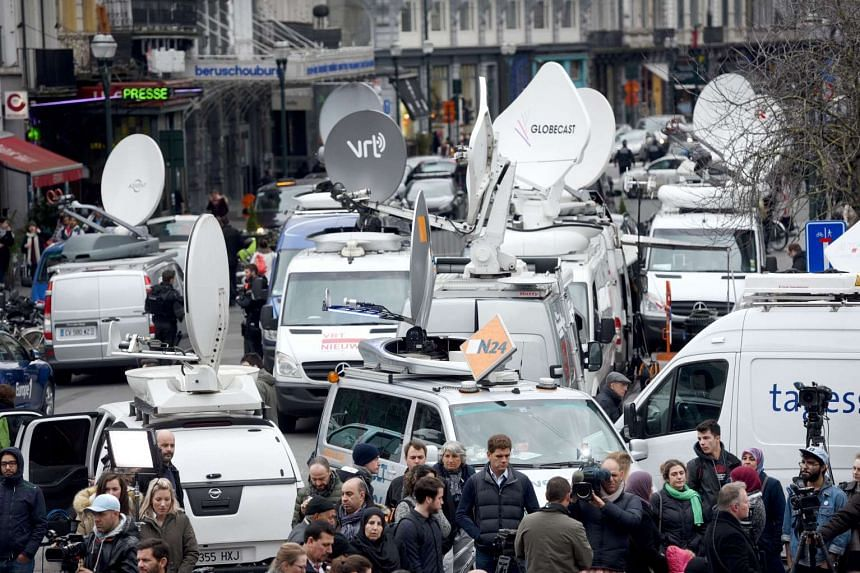 Members of the media gather near Place de la Bourse in Brussels, on March 23, 2016, a day after blasts hit the Belgian capital.