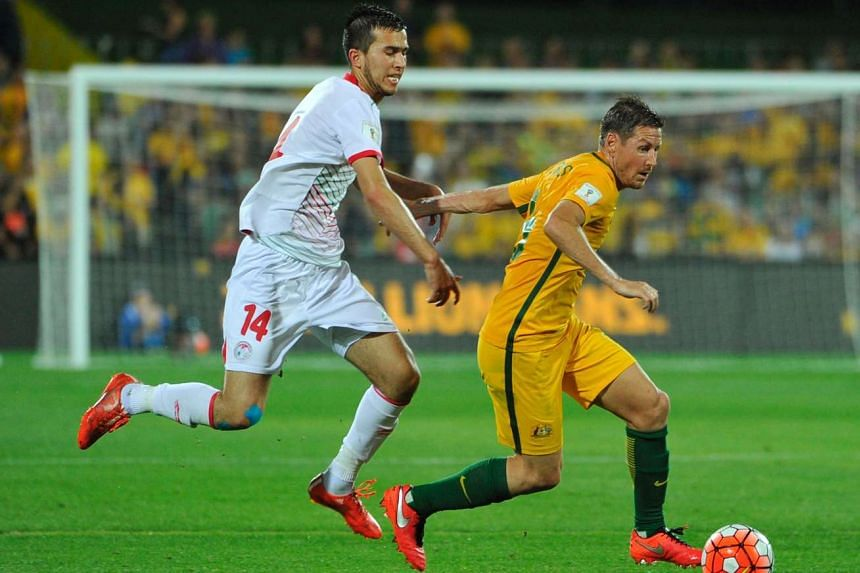 Tajikistan's Sharipov Faridun (left) and Australia's Nathan Burn tussle for the ball in the Fifa World Cup Asian qualifier in Adelaide on March 24, 2016.