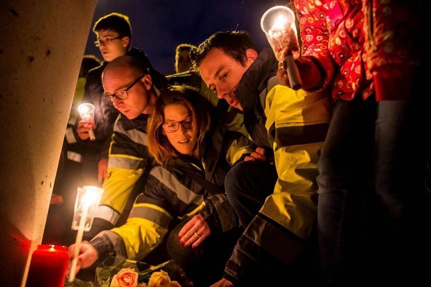 Brussels airport workers and their relatives pay tribute to the victims of Brussels triple attacks near the airport in Zaventem, on March 23, 2016.