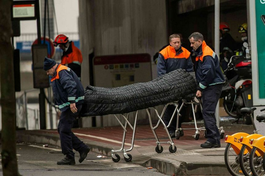 Ambulance men push a stretcher with a body bag, on March 23, 2016, outside the Maalbeek metro station in Brussels.