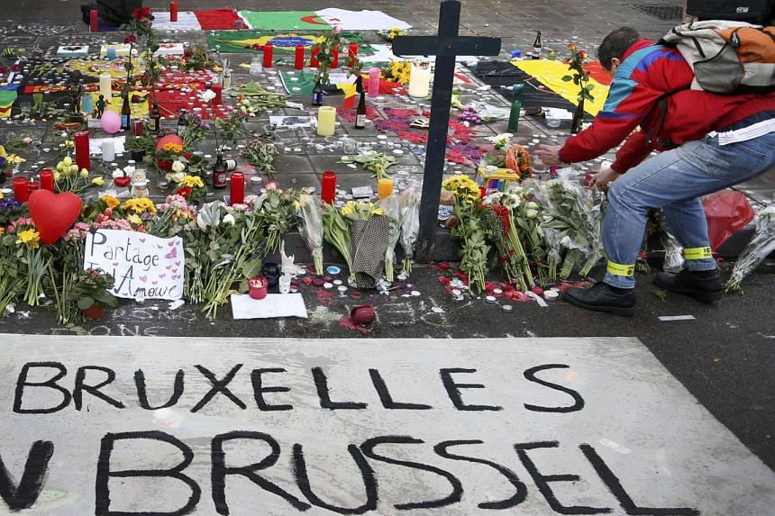 A man places flowers on a street memorial in Brussels.