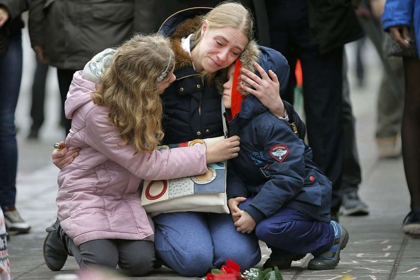 A woman consoles her children at a street memorial following Tuesday's bomb attacks in Brussels, Belgium.