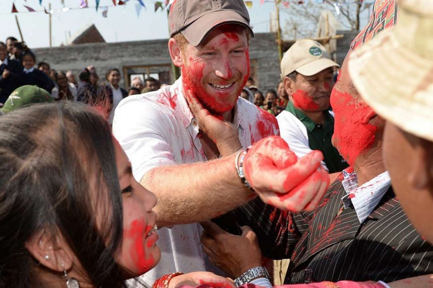 Prince Harry (centre) takes part in the Hindu Holi festival of colour in Nepal on March 22, 2016.