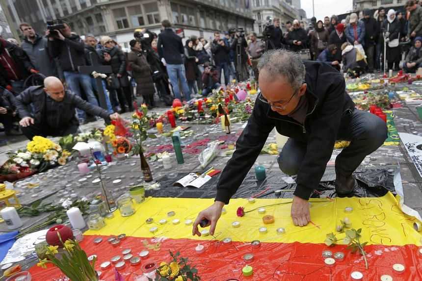 Men place a candles on a street memorial following the bomb attacks in Brussels, Belgium.