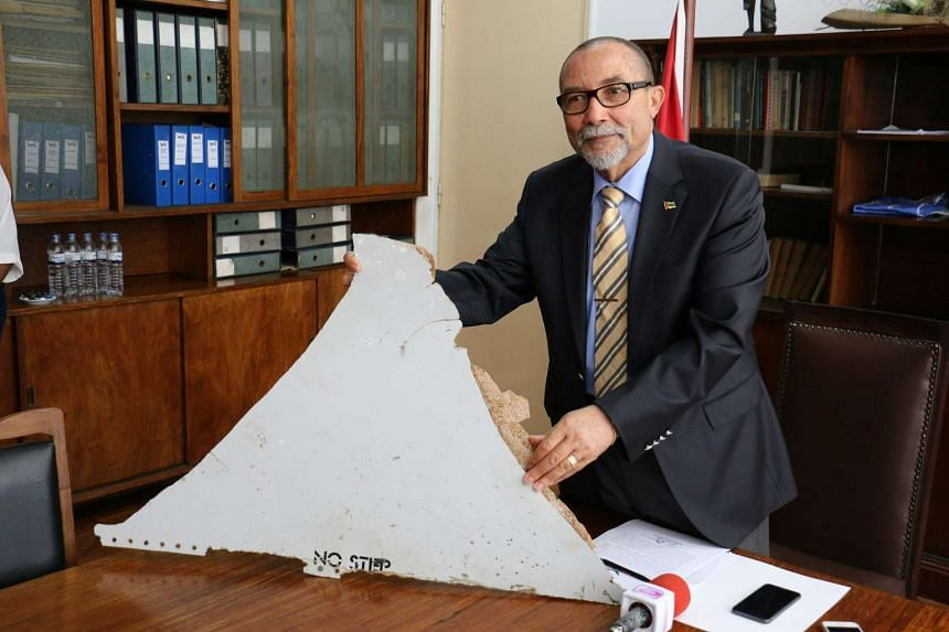 President of Mozambique's Civil Aviation Institute Joao de Abreu holding a piece of suspected aircraft wreckage found off the east African coast of Mozambique.