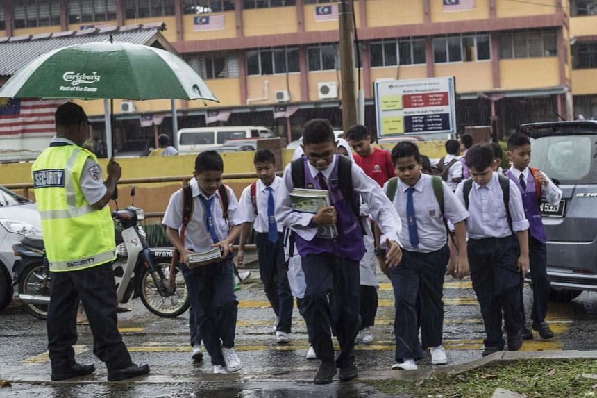 Malaysian students walk out from a school in rain after morning classes in Kuala Lumpur, Malaysia, on March 22, 2016.