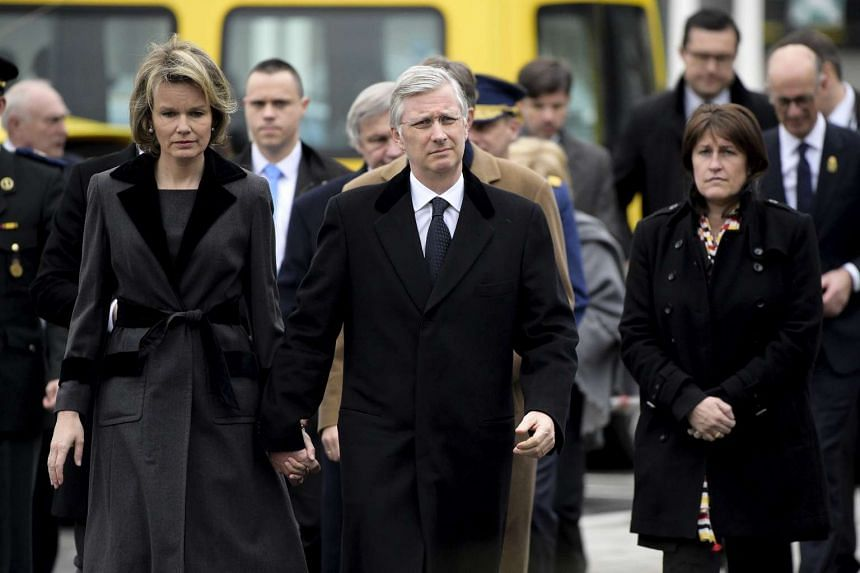 Belgian Queen Mathilde (left) and King Phiippe (centre) attend a ceremony outside of the terminal at Brussels International airport.