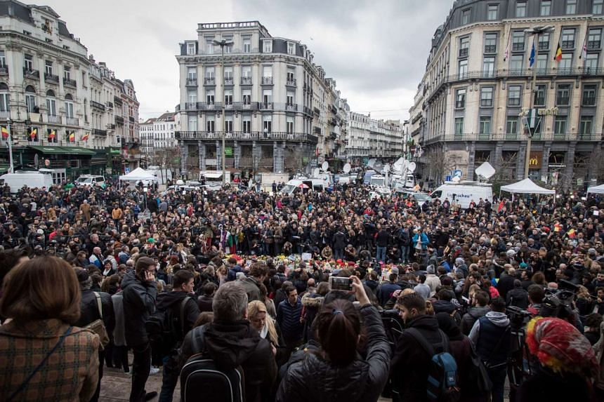 A picture taken on March 23, 2016 in Brussels shows people gathering to pay tribute to the victims, one day after the attacks.