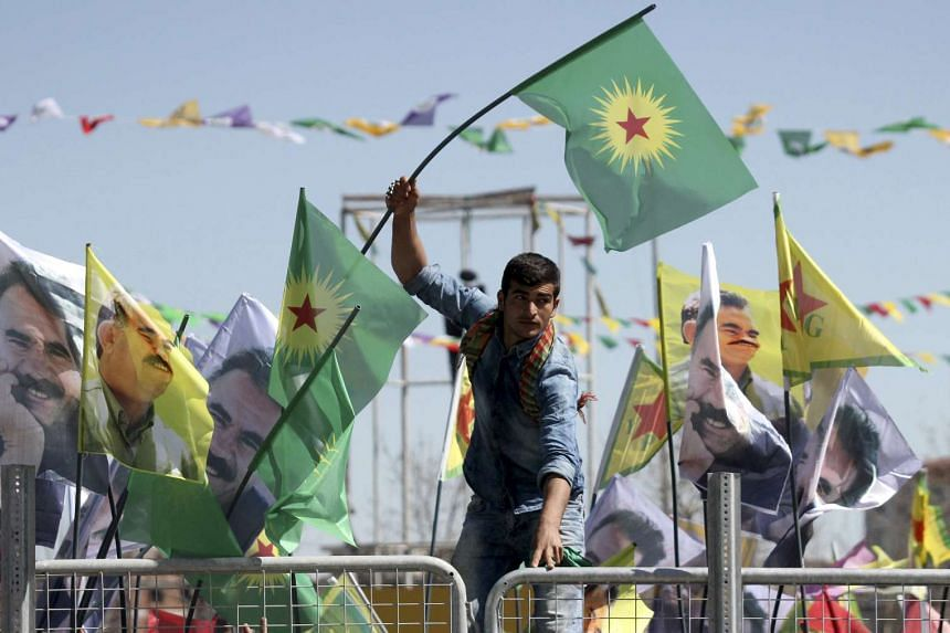 A demonstrator waves a flag of the outlawed Kurdistan Workers Party (PKK) to celebrate the spring festival of Newroz in Diyarbakir, Turkey, on March 21, 2016.