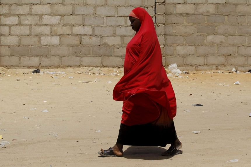A woman walks in a camp for internally displaced people in Maiduguri, Nigeria on March 9, 2016.