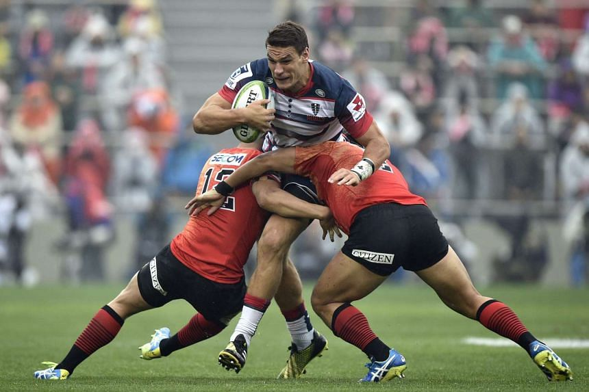 Mitch Inman (centre) of Australia's Rebels is tackled by Yu Tamura (left) and Shota Horie (right) of Japan's Sunwolves.