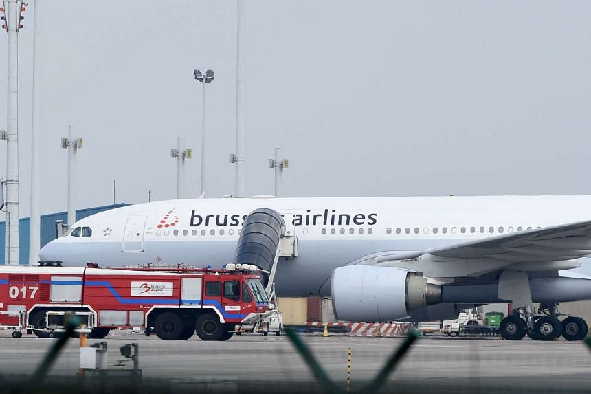 A service vehicle of Brussels Airport parked in front of an airplane of Brussels Airlines at Brussels Airport following twin blasts on March 22, 2016.