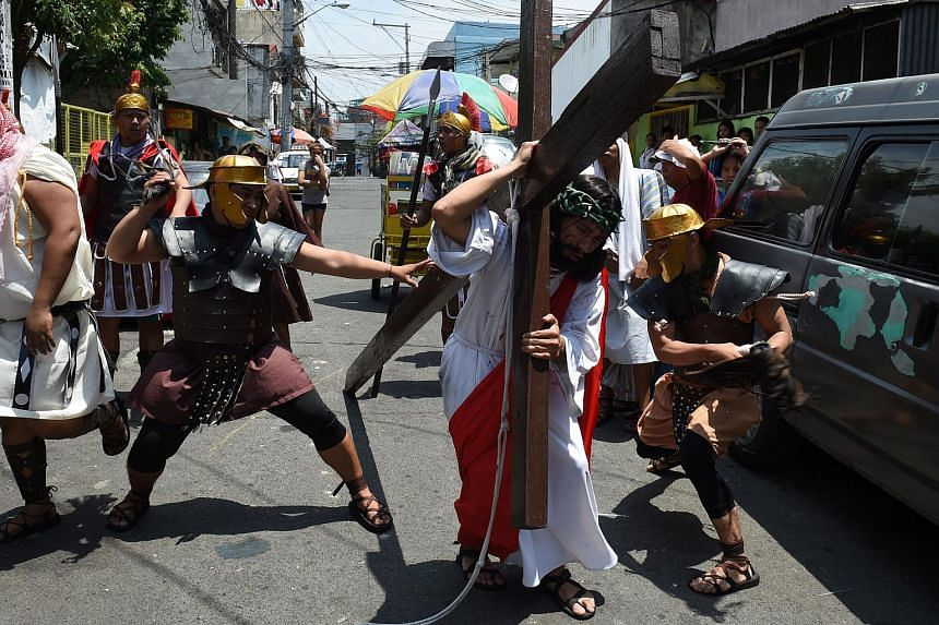 Actors playing the role of Jesus (centre) and Roman soldiers (background) reenacting the suffering and crucifixion of Christ in a street play in Manila on March 24.