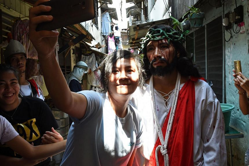 A spectator taking a selfie with an actor playing the role of Jesus in a street play during Holy Week in Manila on March 24.