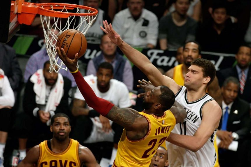 LeBron James (centre) shooting over Brook Lopez (right) in the game between the Brooklyn Nets and the Cleveland Cavaliers on March 24, 2016.