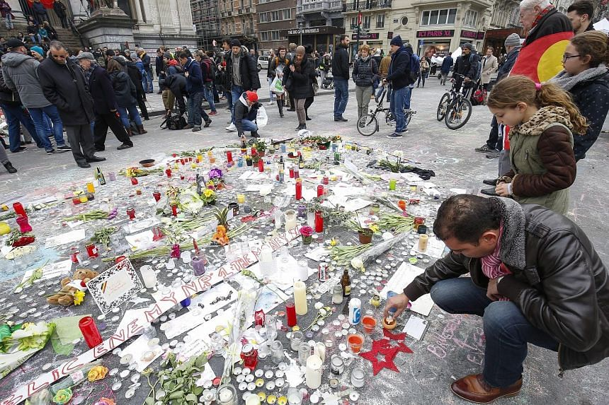 The Bakraoui brothers Ibrahim (top) and Khalid are also suspected of being connected to the Nov 13 terror attacks in Paris that killed 130 people. The many gifts and tributes at the Place de la Bourse in Brussels yesterday in memory of the 31 killed