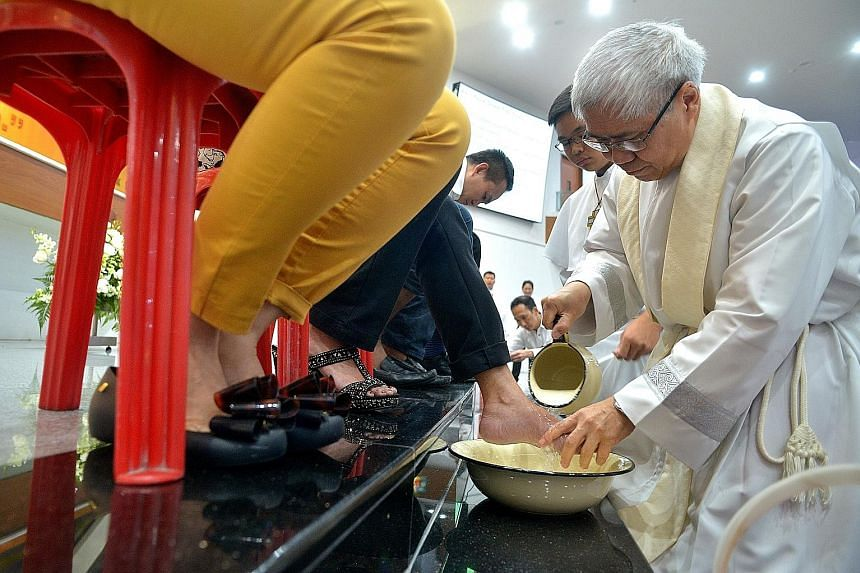 Catholic Archbishop William Goh washing the feet of one of 12 parishioners at the Church of the Holy Cross, as part of its annual Maundy Thursday mass. Half of them were women, a first this year following a new ruling issued by Pope Francis in Januar